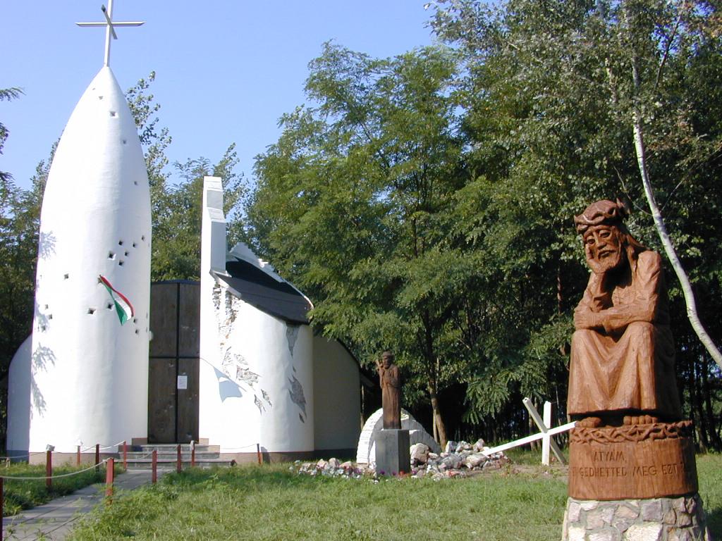 ELKÉSZÜLT A SZOBOR. Az 1956-os áldozatok tiszteletére emelt kiskunmajsai Kapisztrán Szent János kápolna elõtt már felállították az ülõ Krisztus szobrát. Az alkotást az a Rimantas Zinkevicius készítette, akinek nevéhez eddig két majsai faszobor - a Szabadulás szobor (1991) és a mayossaszállási piétás emlékmû (2000) - felállítása fûzõdik. A kápolna a város központjától négy kilométerre, a Szeged felé vezetõ mûút mellett található, átellenben a Pongrátz Gergely-féle '56-os emlékmúzeummal. A Krisztus-szobor - melyet augusztus 19-én délután négy órakor szentelnek fel - felirta: Atyám, hogy engedhetted meg ezt? FOTÓ: TAPODI KÁLMÁN